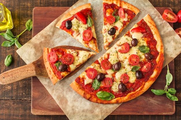 Pizzascheiben auf marmor über dem schneidebrett Kostenlose Fotos