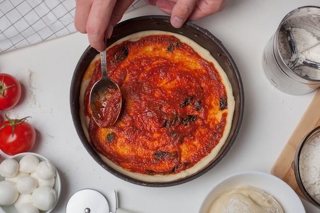 Pizzateig mit zutaten und tomatensauce. Premium Fotos