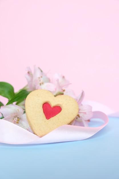 Plätzchen in form eines herzens mit einem rosa band auf einem rosa Premium Fotos
