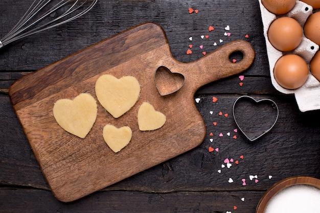 Plätzchen, küchenwerkzeuge und herzen auf holz Premium Fotos
