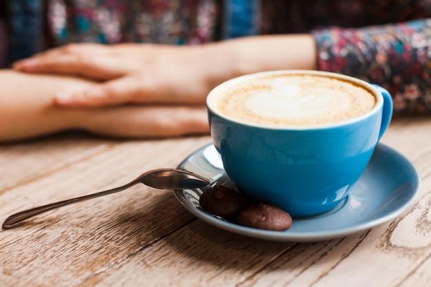 Plätzchen und lattekaffeetasse vor der frau, die im cafã © sitzt Kostenlose Fotos