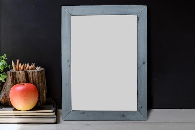 Plakatmodell mit apfel auf dem buch auf holztischschwarzfarbwandhintergrund Premium Fotos
