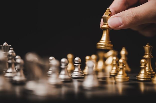 Planen sie die führende strategie eines erfolgreichen geschäftswettbewerbsführerkonzepts, das schachbrettspiel der hand des spielers, das goldbauern setzt Premium Fotos