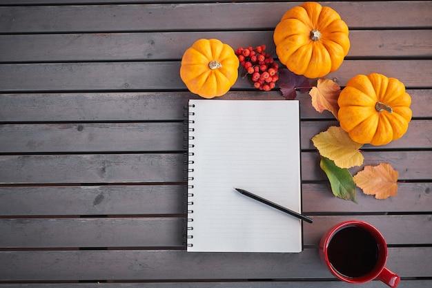 Planen sie eine liste der herbststimmungskomposition auf einem holztisch mit kürbis-eberesche und blättern. öffnen sie notizblock und kaffee in der roten tasse und auf dem grauen holztisch Premium Fotos