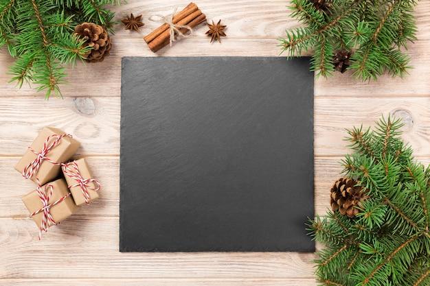 Planen sie tafel auf holztisch mit weihnachtsdekoration, schwarzen schieferstein auf hölzernem, konzept des neuen jahres Premium Fotos