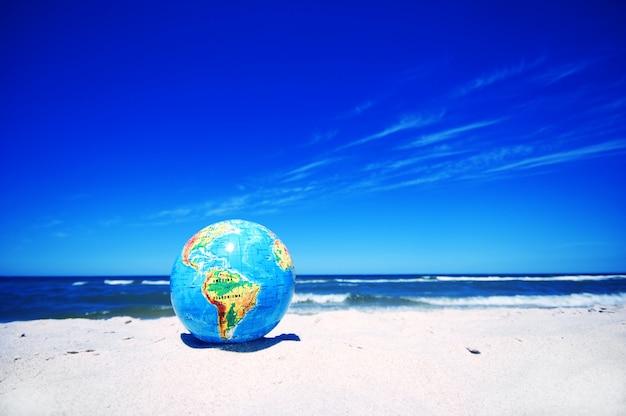 Planeten erde auf sandstrand Kostenlose Fotos