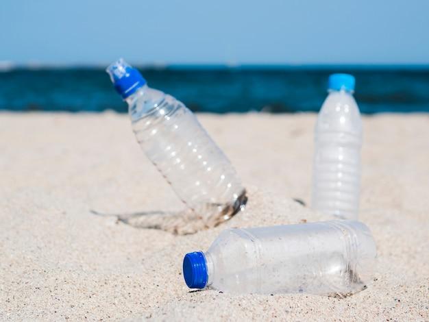 Plastikabfall leere flasche auf sand am strand Kostenlose Fotos