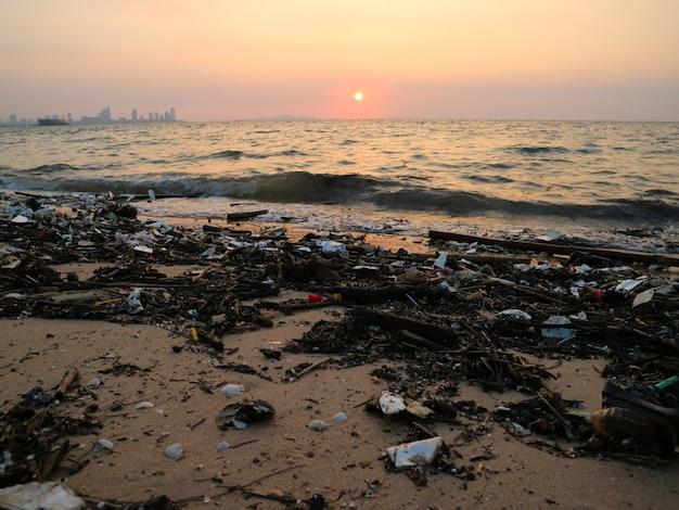Plastikbambusschaum und abfallverschmutzung auf strandsonnenunterganghintergrund Premium Fotos