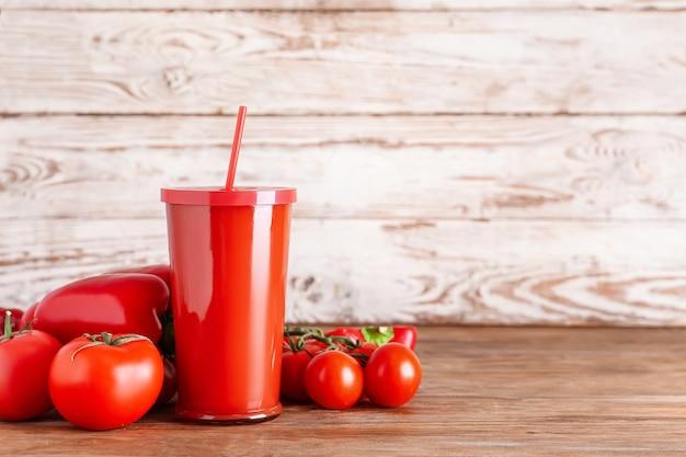 Plastikbecher des gesunden smoothie mit tomate und paprika auf holzoberfläche Premium Fotos