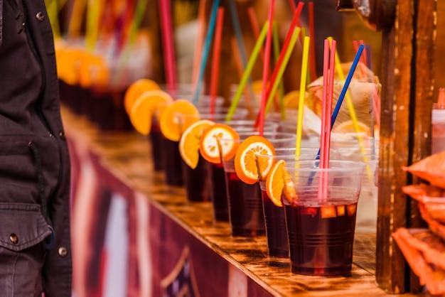 Plastikbecher mit erfrischenden alkoholischen getränken mit orangenscheiben und farbigen strohen an einem sommerfestival. Premium Fotos