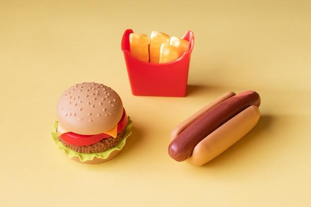 Plastikburger, salat, tomate, kartoffeln mit einem hotdog auf einem gelben hintergrund bratend Premium Fotos