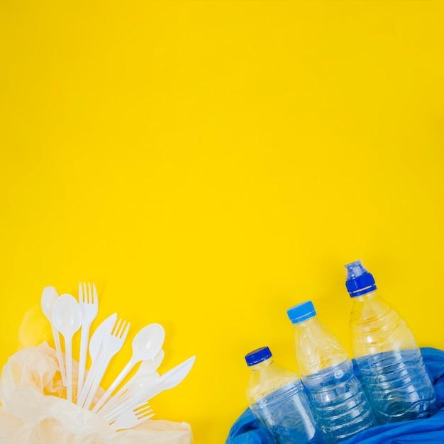 Plastikgabel und löffel mit leerer plastikflasche in der plastiktasche über gelbem hintergrund Kostenlose Fotos