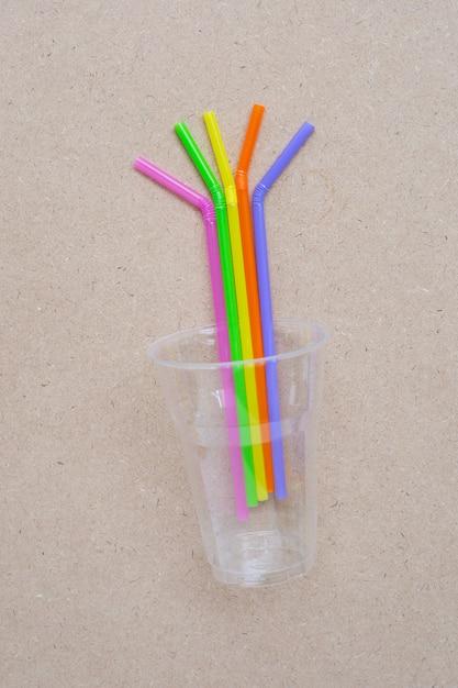 Plastikglas mit strohhalmen auf sperrholz Premium Fotos