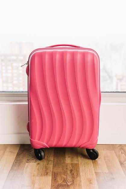 Plastikkoffer der rosa reise mit rädern auf bretterboden Kostenlose Fotos