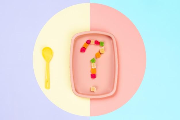 Plastikrosa platte, auf der ein fragezeichen der kandierten ananas und des gelben löffels in einem gelb-rosa lokalisierten hintergrund ist. Premium Fotos