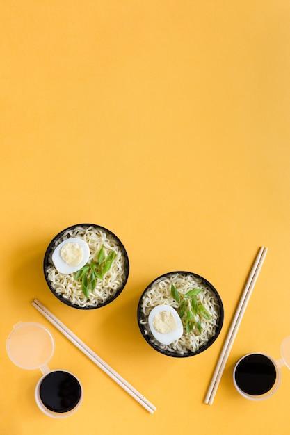 Plastikschalen von instantnudeln mit eiern essstäbchen und sojasauce auf papierhintergrund kopieren raum. Premium Fotos