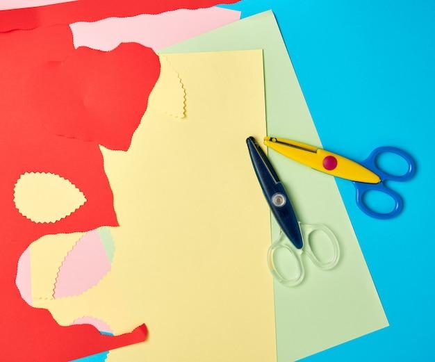 Plastikschere und farbiges papier zum schneiden von figuren Premium Fotos