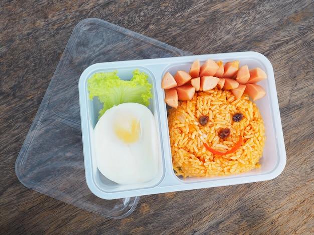 Plastikschulbrotdose für kinder mit lustigem gesicht des gebratenen reises und des eies Premium Fotos