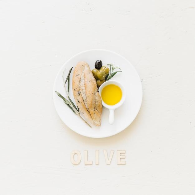 Platte mit brotoliven und -öl mit olivgrünem wort Kostenlose Fotos