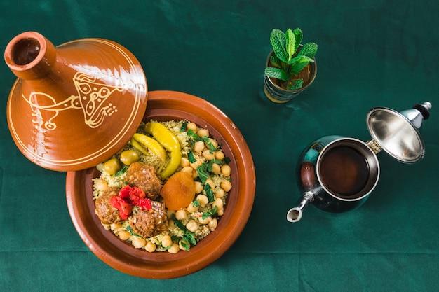 Platte mit essen in der nähe von tasse getränk und teekanne Kostenlose Fotos