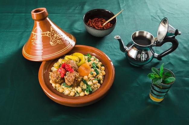 Platte mit essen in der nähe von trockenen früchten, tasse getränk und teekanne Kostenlose Fotos