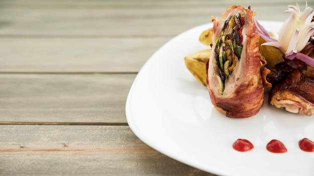 Platte mit gebratenen fleischrouladen- und kartoffelkeilen auf holztisch Kostenlose Fotos