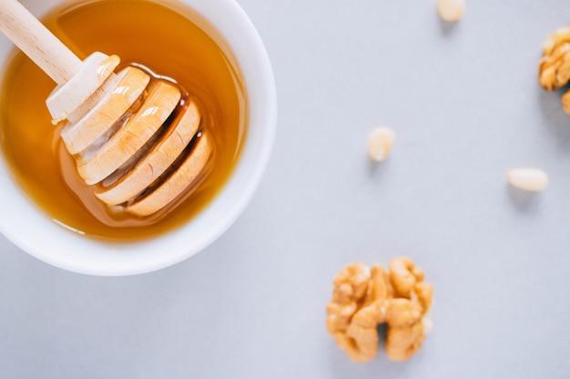 Platte mit honigschöpflöffel, walnüssen und kiefernnüssen auf einem weißen hintergrund, draufsicht Premium Fotos