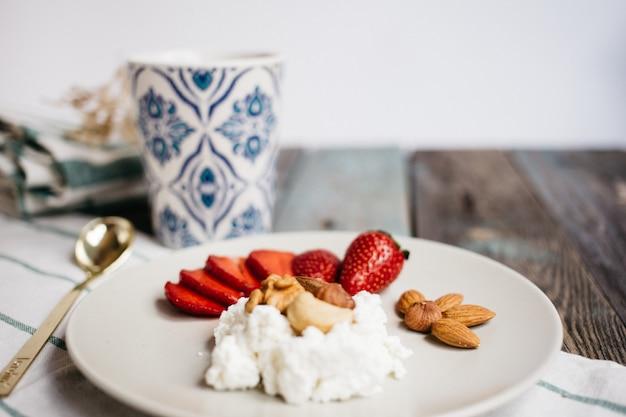Platte mit hüttenkäse, erdbeeren und nüssen, einem tasse kaffee und tüchern auf holztisch, gesundes lebensmittel, frühstück Premium Fotos