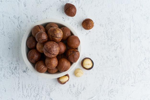 Platte mit mandeln in endocarp, ganze und gehackte nüsse in loser schüttung auf schneidebrett Premium Fotos