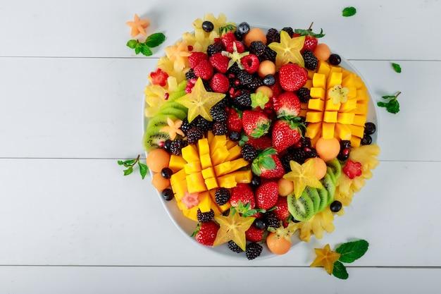 Platte mit mango, orangen, kiwi. erdbeeren, heidelbeeren. Premium Fotos