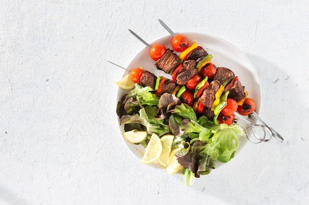 Platte mit rindfleisch gegrillt und salat Premium Fotos