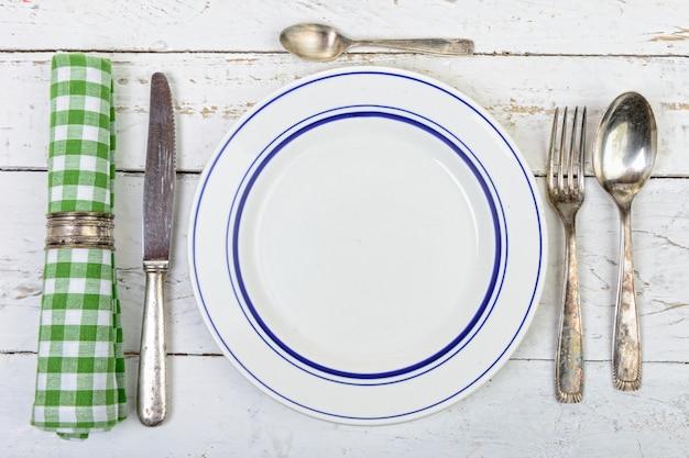 Platte mit silbernem tischbesteck auf einer alten weißen tabelle Premium Fotos