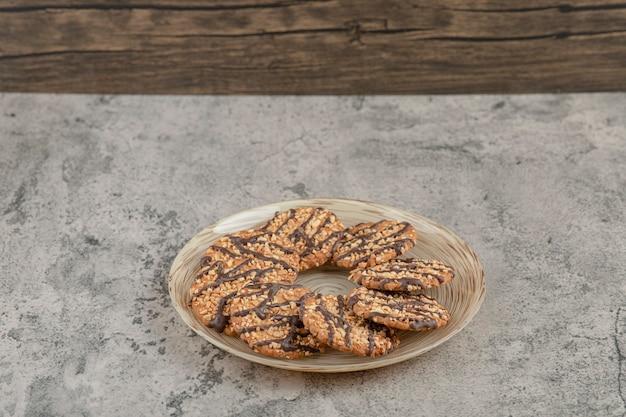 Platte voll von süßen haferkeksen mit schokoladensirup auf einem steinhintergrund. Kostenlose Fotos