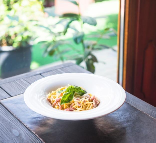 Platte von teigwarenspaghettis mit basilikum verlässt auf placemat über der tabelle Kostenlose Fotos