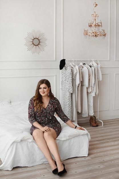 Plus size model girl in einem modischen kleid in einem schlafzimmer interieur. junge pralle frau mit hellem make-up und mit stilvoller frisur, die im innenraum aufwirft. xxl mode. körper positiv Premium Fotos