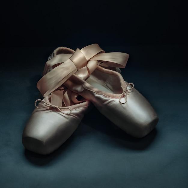 Pointe beschuht balletttanzschuhe mit einem bogen der bänder, die auf einem dunklen hintergrund schön gefaltet werden. Premium Fotos