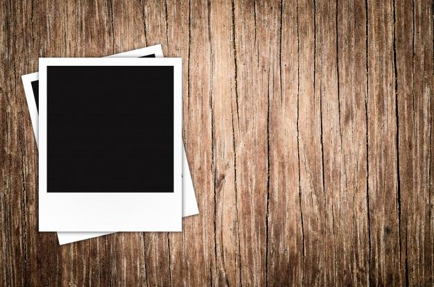 Polaroidfotorahmen auf hölzernem hintergrund Premium Fotos