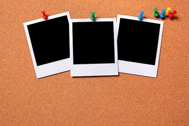 Polaroidfotos zu einem kork brett geheftet Kostenlose Fotos