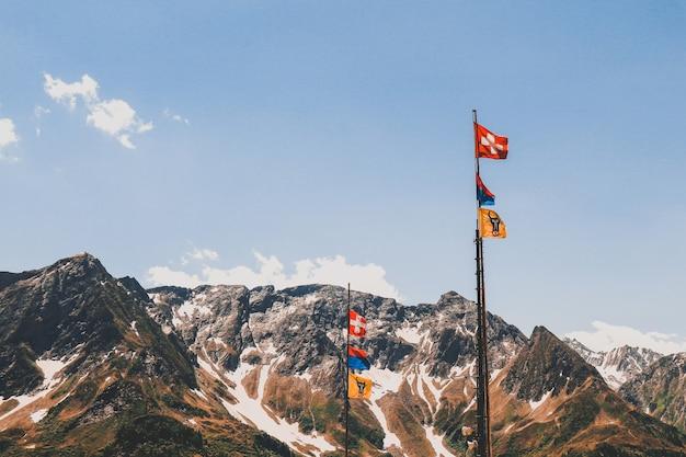 Pole mit fahnen in den schönen felsigen bergen bedeckt mit schnee unter dem bewölkten himmel Kostenlose Fotos