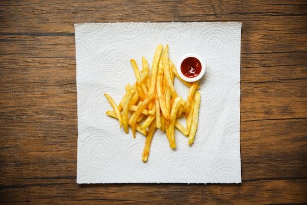 Pommes-frites auf weißbuch mit ketschup auf hölzernem Premium Fotos