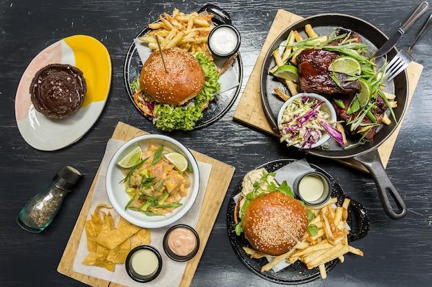 Pommes-frites, ceviche, rippen und muffins burgersm auf einem holztisch Premium Fotos