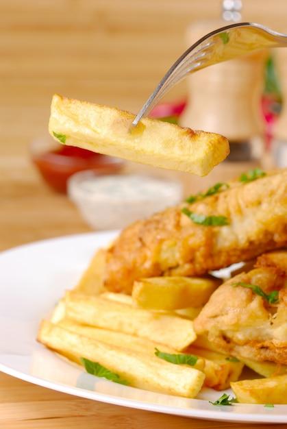 Pommes frites, fisch, dips und gewürze Premium Fotos
