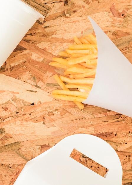 Pommes-frites im weißen kegel auf hölzernem strukturiertem hintergrund Kostenlose Fotos