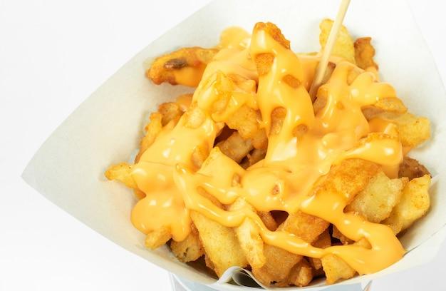 Pommes-frites in der weißen schale mit käsesoße auf weißem hintergrund Premium Fotos