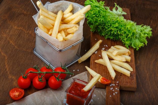 Pommes-frites in einem gitter mit ketchup-, salat- und kirschtomaten auf hölzerner brauner tabelle Premium Fotos