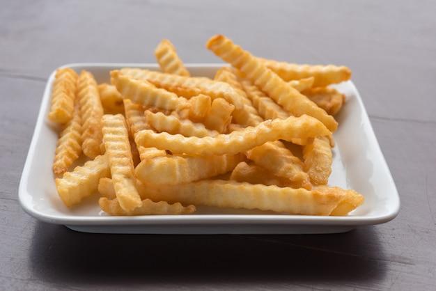 Pommes-frites in einer weißen platte auf einem holztisch. Premium Fotos