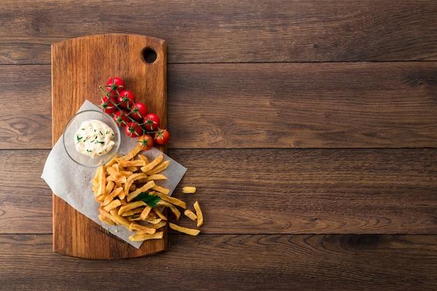 Pommes frites, kirschtomaten, knoblauchsauce auf holz Premium Fotos