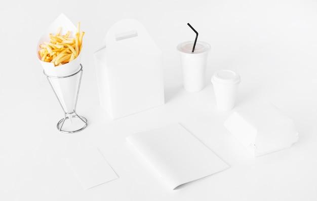 Pommes frites mit essenspaket und entsorgungstasse Kostenlose Fotos