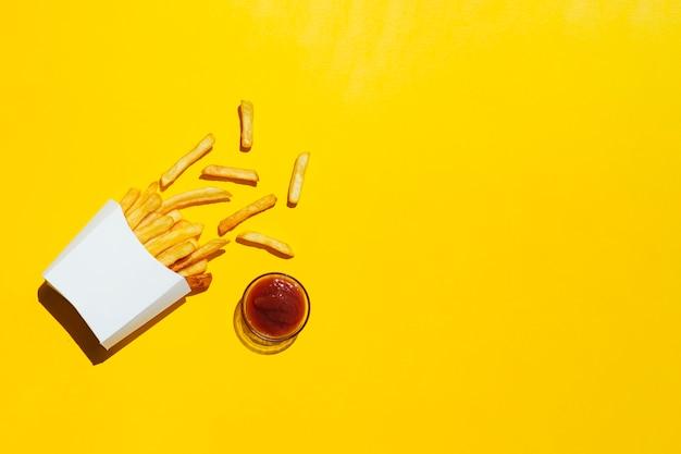 Pommes-frites mit ketschup auf gelbem hintergrund Kostenlose Fotos