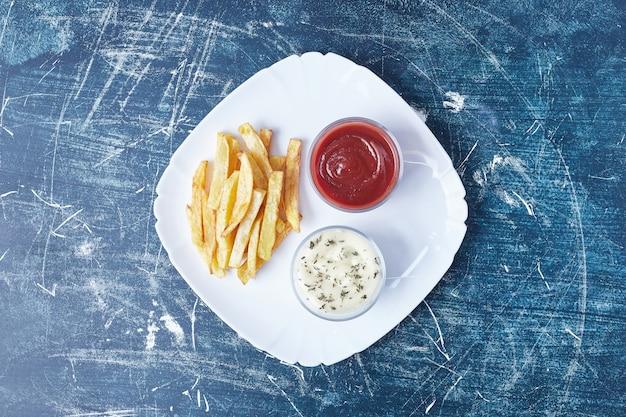 Pommes frites mit saucen in einem weißen teller. Kostenlose Fotos